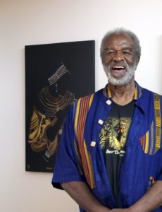 "TheArthur Wright, in front of his bleach painting titled ""Maasai Thinker"""